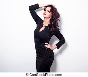 Portrait of a beautiful adult sensuality woman in black dress posing over white background. Sight at the camera