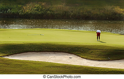 Golfer putting on green - Image of a golfer putting on green
