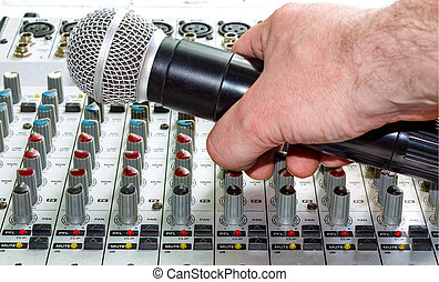 Hand with microphone - Hand with a microphone on the audio...