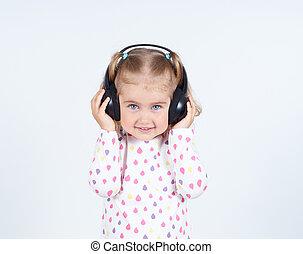 Little girl listening to music on headphones.