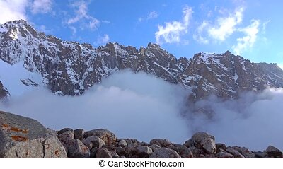 Hiker walks on rocks against cloudy snow covered mountains...