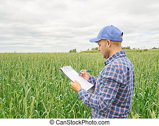 Farmer in plaid shirt controlled his field and writing notes...