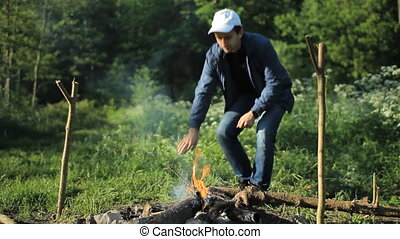 Man fire up campfire - White man with white cap try to fire...