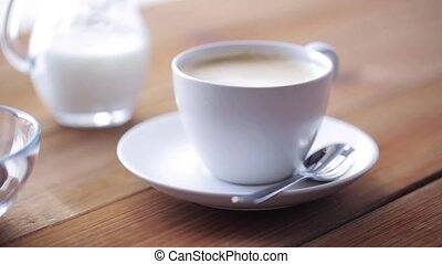 coffee cup and beans pouring to wooden table
