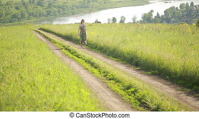 girl goes on a rural road summer evening a green dress