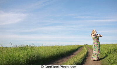 girl goes on a rural road. summer evening. a green dress