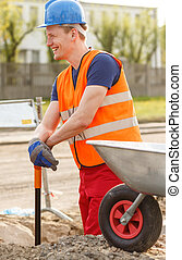 Smiling building worker with a shovel and wheelbarrow