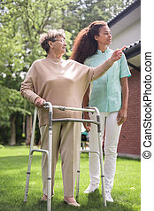 Female with walking zimmer - Image of carer and female with...