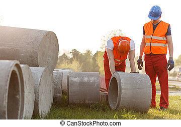 Construction worker rolling concrete pipe - Strong...