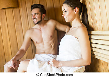 Young couple relaxing in the sauna - Happy couple sitting in...