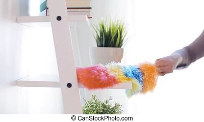 woman with duster cleaning dust from shelf at home - people,...