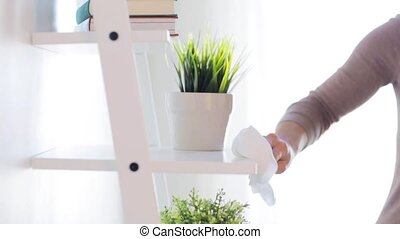 woman with duster cleaning shelf from dust at home - people,...