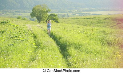 Running woman. Girl jogging on trail in mountains on field with grass in summer.