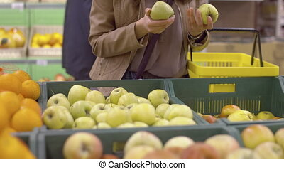 Cute girl chooses fresh apples at the supermarket in the...