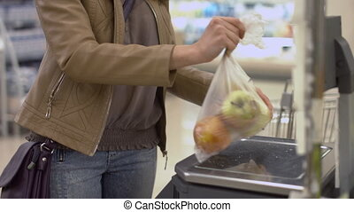Beautiful girl weighing the apples in a bag at the store -...