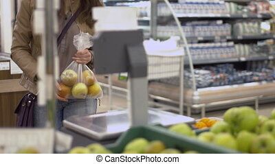 Beautiful girl weighing the apples in a bag at the store