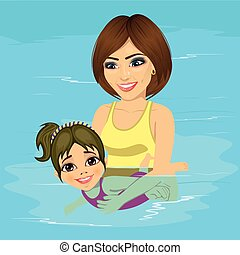beautiful young mother teaching her little girl how to swim at swimming pool