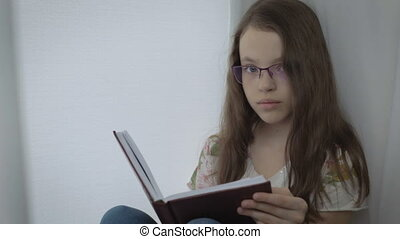 Serious little girl in glasses diligently does his homework...