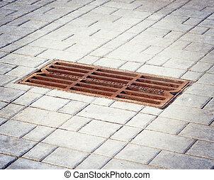 Sidewalk & hatch sewer manhole.