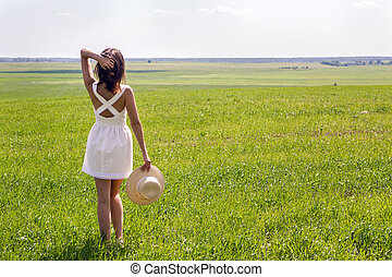 young girl with long dark hair standing on a green field