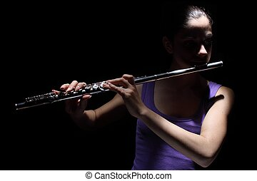 Girl playing a flute - Girl in lavender shirt playing a...