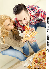 Pizza time - Couple relaxing at home and eating pizza,having...