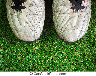 Old muddy dirty football shoes on artificial grass