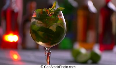 Glass of beverage is rotating. Coktail with mint and lime....