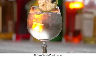 Glass with drink and ice Tongs put lemon into beverage Cold...