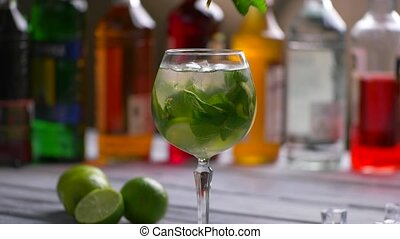 Mint branch and green cocktail. Hand puts mint into...