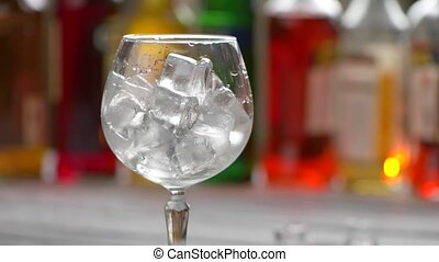 Jigger pours drink into glass. Wineglass filled with ice....
