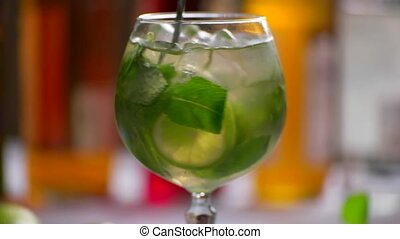 Green drink in a glass. Spoon rapidly mixing beverage. Juicy...