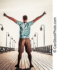 Man on pier with raised hands arms Freedom - Man tourist on...