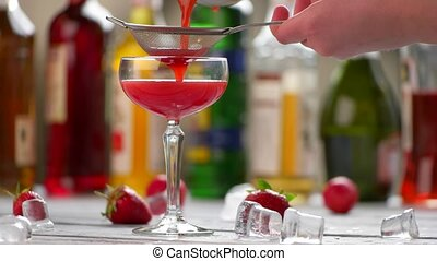 Red beverage in a glass. Hand holding sieve over glass....