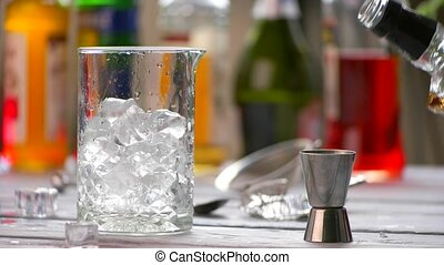 Jigger and jug with ice. Bottle pouring drink into jigger....