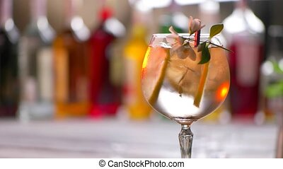 Flower on glass with drink. Glass with beverage is rotating....