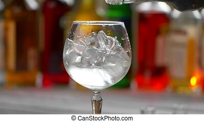 Bottle pours beverage into glass. Wineglass with ice cubes....