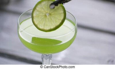 Tongs put lime into cocktail. Green beverage with lime...