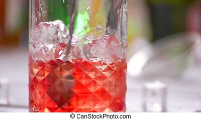 Spoon mixing cocktail in jug. Red drink in transparent jug....