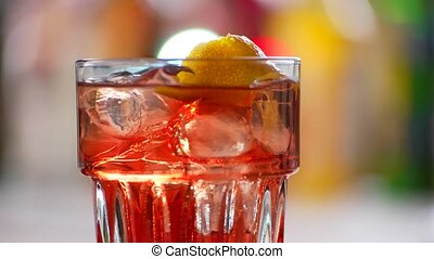 Glass of cocktail rotates. Red drink with lemon peel....