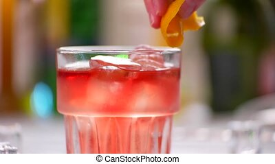 Glass with red drink. Beverage with lemon peel. Bartender...