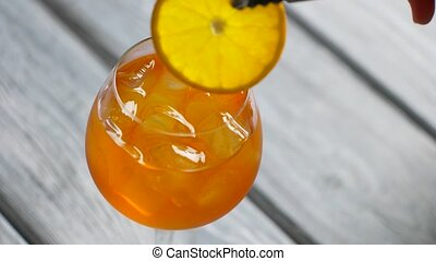 Tongs put orange into cocktail.