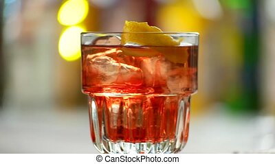 Glass of negroni is rotating. Red beverage with ice. Sweet...