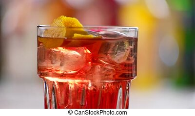 Glass with red cocktail rotates. Lemon peel inside a drink....