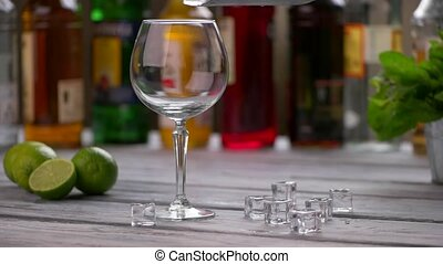 Ice cubes falling into glass. Limes beside a wineglass....