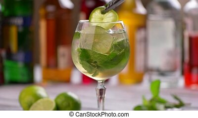 Tongs put lime into beverage. Drink with mint and lime. Hugo...