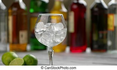 Mint leaves fall into glass. Wineglass with cubes of ice....
