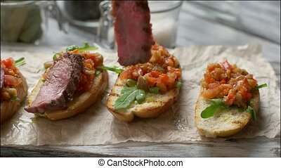 Tongs put meat on vegetables Grilled toasts with vegetables...