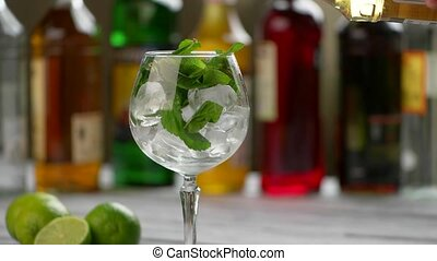Bottle pours drink in glass. Wingelass with ice and mint....