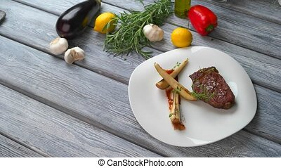 Paprika near plate with meat. Cooked meat and tongs. Hot...